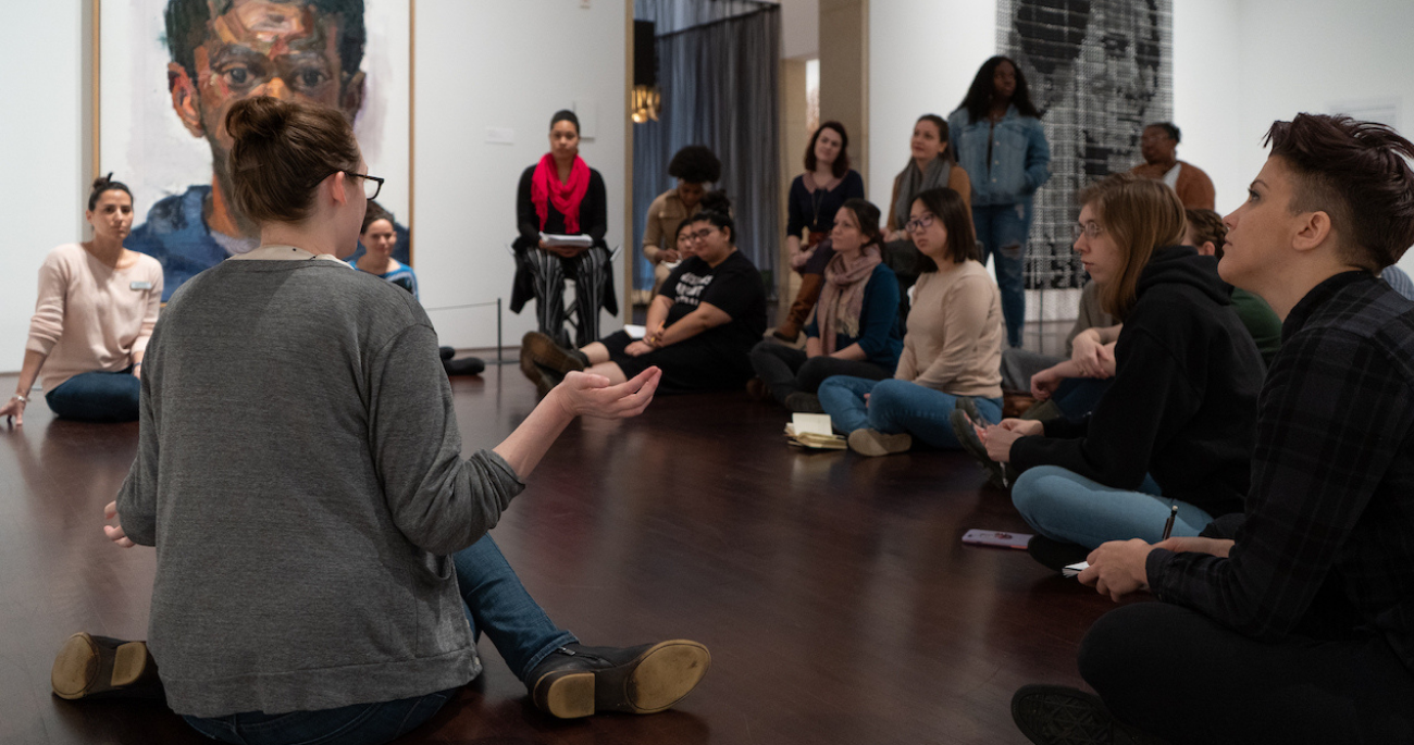 A teacher sits on the floor of a gallery, talking to other people who are sitting and standing.